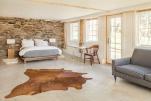Milkweed Barn, Converted Barn, bedroom, concrete floor, exposed stone foundation wall, exterior door, nicole vidor, real estate, realtor